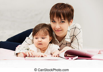 Mother and little baby girl reading a book on bed