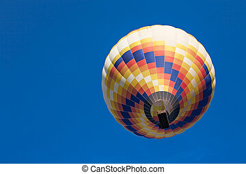 Colorful hot-air balloon in flight seen from below