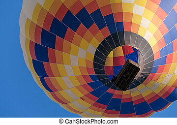 Closeup of a colorful hot-air balloon in flight seen from below