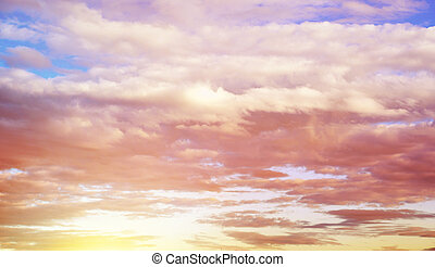 Fluffy clouds floating over the sunset sky