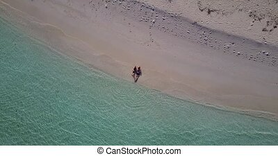 v04021 Aerial flying drone view of Maldives white sandy beach 2 people young couple man woman romantic love on sunny tropical paradise island with aqua blue sky sea water ocean 4k