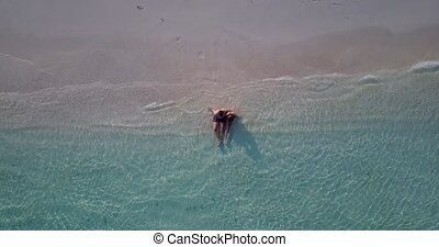 v04013 Aerial flying drone view of Maldives white sandy beach 2 people young couple man woman romantic love on sunny tropical paradise island with aqua blue sky sea water ocean 4k
