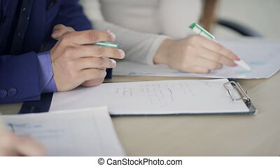 Male and female hands are writing on paper at the desk. The...
