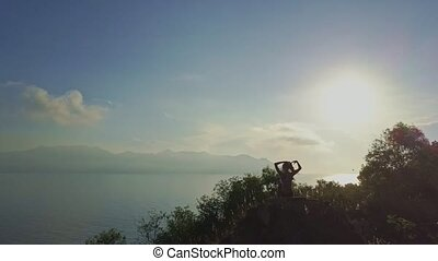 Slim Girl Sits on Steep Cliff Smooths Hair at Dawn -...