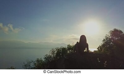 Drone Approaches Girl Resting on Cliff under Morning...