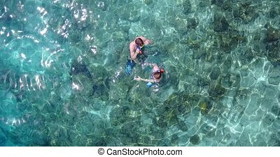 v04075 Aerial flying drone view of Maldives white sandy beach 2 people young couple man woman snorkeling swimming diving on sunny tropical paradise island with aqua blue sky sea water ocean 4k
