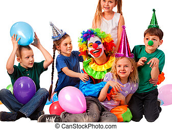 Birthday clown playing children. Kid wearing party hat hold...