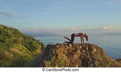 Slim Athletic Girl Does Exercises on Steep Cliff in Morning...