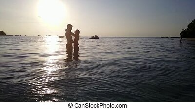 v04113 Aerial flying drone view of Maldives white sandy beach 2 people young couple man woman romantic love sunset sunrise on sunny tropical paradise island with aqua blue sky sea water ocean 4k