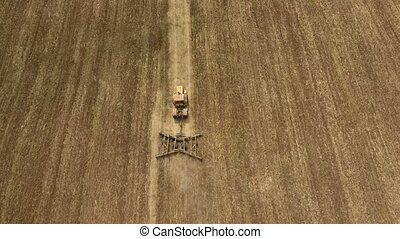Aerial shot of a Ukrainian field and a powerful tractor...