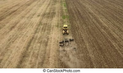 Aerial shot of a rural field and a big tractor pulling a...
