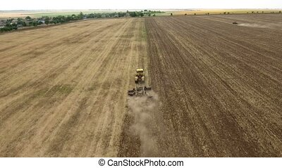Aerial shot of a rural field and a farm tractor pulling a...