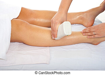 Beautician waxing woman leg - Beautician waxing womans leg...