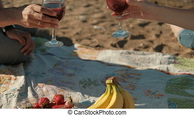 Couple sitting on beach, evening picnic drinking wine with fruit