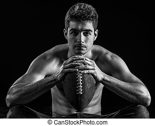Football player portrait holding american football staring.
