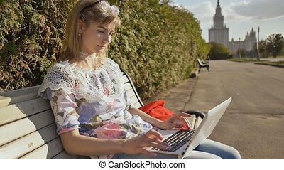 Girl in the fresh air typing on the keyboard of a white...