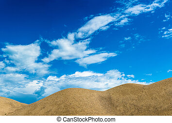 Sand dunes on the background of beautiful cloudy sky.