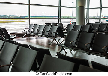 Empty airport terminal waiting area with chairs. - Empty...