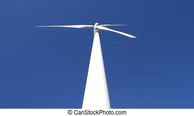 Wind turbine on blue sky - White wind turbine rotating at...