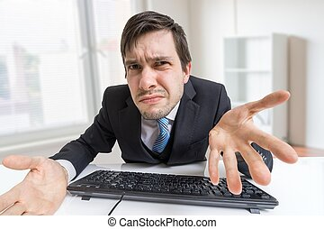 Frustrated confused and unsure man is working with computer...