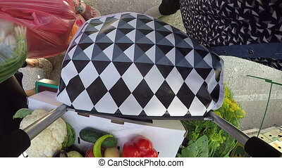 POV: Senior woman with rolling grocery bag shopping at local...