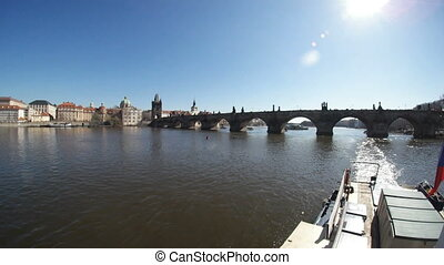 The Charles bridge in Prague shot from a motorboat on the Vltava river in spring