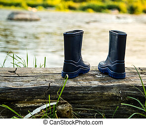children's rubber boots on a log