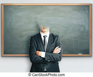 Headless businessman on blackboard background - Abstract...