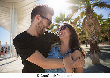 Happy couple cuddling and laughing together outside
