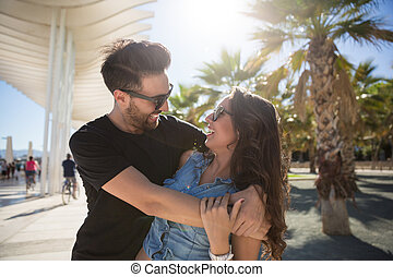 Happy young couple embracing together in sun light