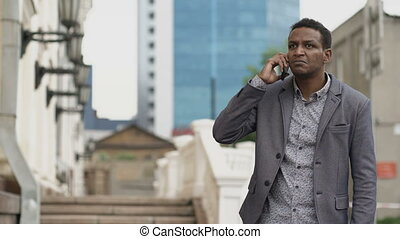 Angry businessman talking mobile phone and swearing with his employee outdoors
