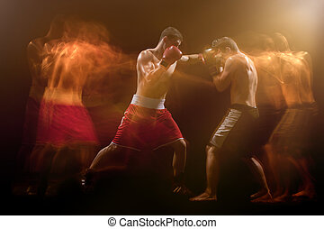 The two male boxers boxing in a dark studio - The two male...