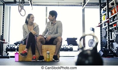 Beautiful young fit couple in modern crossfit gym talking. -...