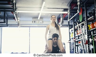 Man carrying woman on his shoulders, doing squats. - Young...