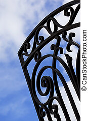 Wrought iron gate and cloudy sky on background