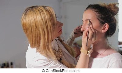 Make up artist working on a model before shooting. Art and...