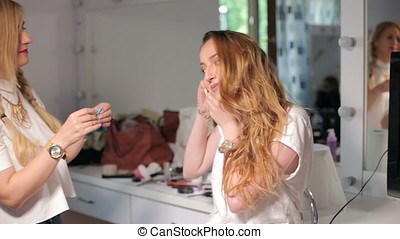 Artist applying makeup to a model before shooting. Art and...