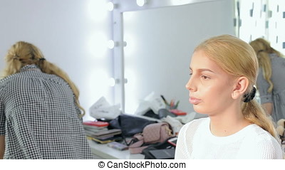 Make-up artist getting ready a model for photoshooting....