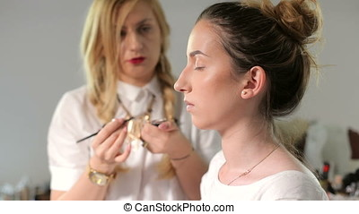 Make-up artist getting a model ready for shooting. Beauty...