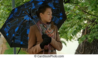Beautiful young woman standing under an umbrella. Bad news,...
