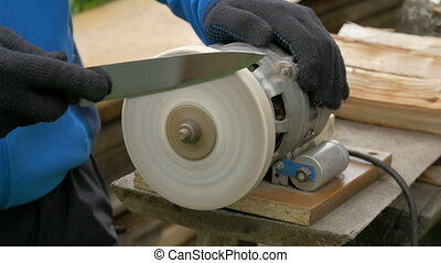 A specialist sharpens a table knife. - Work on a sharpening...