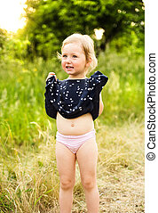 Cute little girl outside in in green sunny summer nature. -...