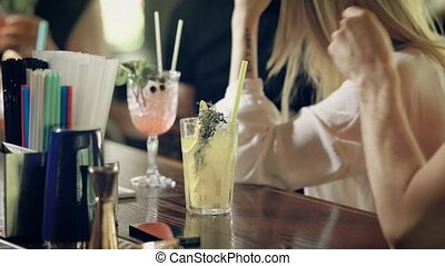 Close up view of people in the bar and thair cocktails