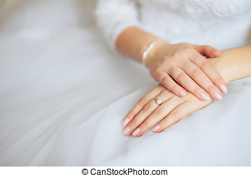 Hands of the bride with a manicure on a white dress