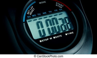 Stopwatch Counts To 10 Closeup On Black - Closeup of a...