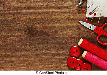 Sewing tools in shades of red on wooden table