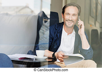 Cheerful businessman using cellphone for communication -...