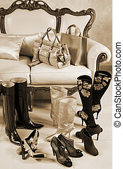 Female shoes, boots and handbags on a background of a sofa...