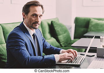 Busy man in suit typing on modern computer - Portrait of...