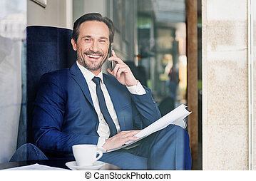 Glad male manager using cellphone for communication - I...
